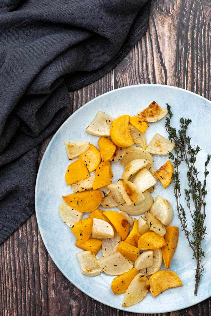 plate of roasted turnips with thyme sprig and napkin